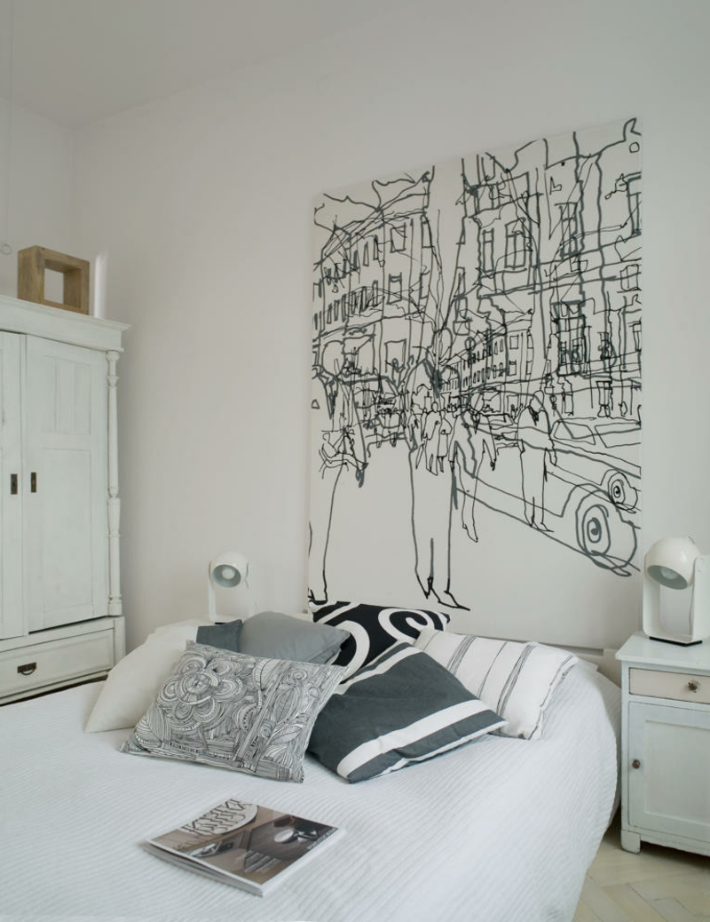 Patterned cushions on double bed in white bedroom with artwork above bed in modern loft apartment, Katowice, Poland