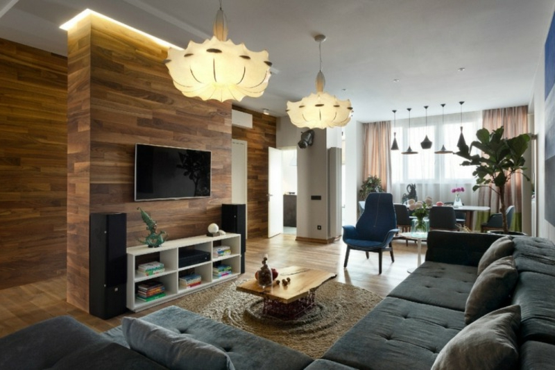 Wohnzimmer mit Wandverkleidung aus Holz und graues Ecksofa