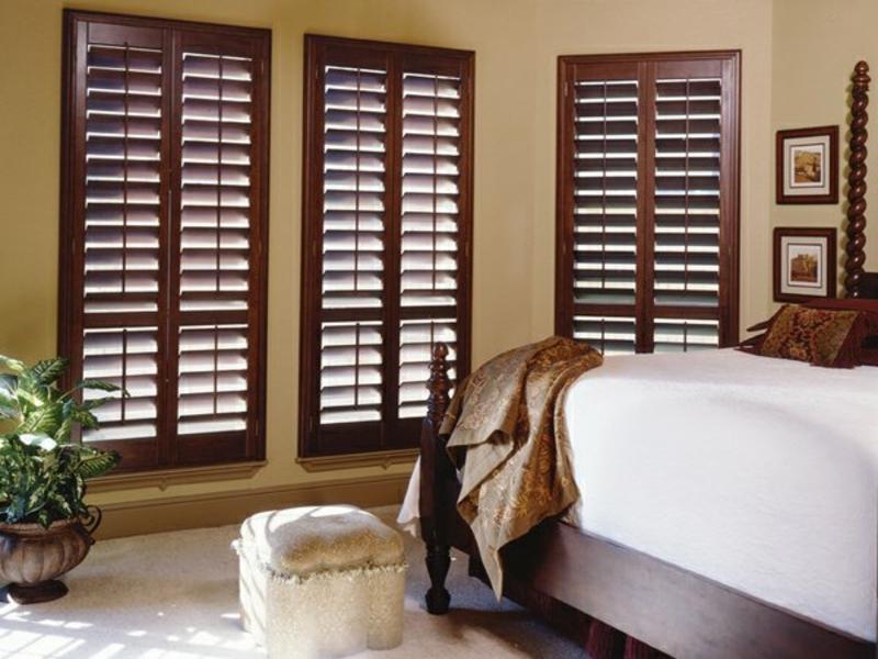 Schlafzimmer mit Holzjalousien in einer Dunkelfarbe