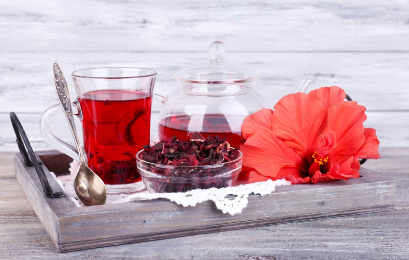 Hibiscus tea in glass teapot and flower on color napkin on wooden background