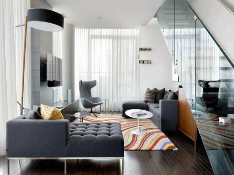 buntes wohnzimmerteppich und graue möbel