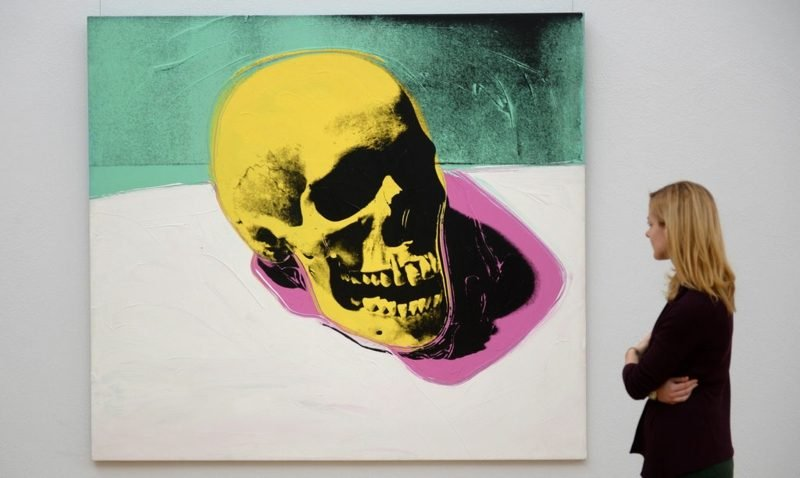 epa04498086 A woman looks at the work 'Skull' (1976) by US artist Andy Warhol during a preview of the exhibition 'Andy Warhol - Death and Disaster' at the 'Kunstsammlung Chemnitz' museum in Chemnitz, Germany, 21 November 2014. The 61 pieces of Warhol's group of works entitled 'Death and Disaster' are on display at the museum until 22 February 2015. EPA/HENDRIKSCHMIDT