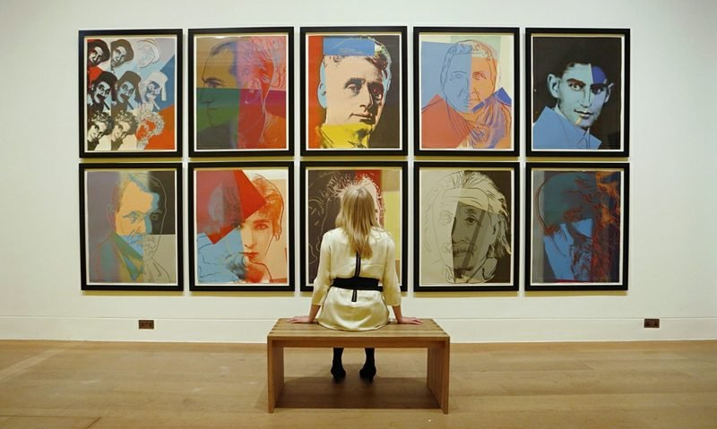"""Gallery employee Maddy Adeane poses with Andy Warhol's """"Ten Portraits of Jews of the Twentieth Century"""" (1980) at the Dulwich Picture Gallery in London June 19, 2012. The exhibition """"Andy Warhol: The Portfolios"""", on show in Europe for the first time, runs from June 20 until September 16, 2012. REUTERS/Luke MacGregor (BRITAIN - Tags: ENTERTAINMENT SOCIETY) - RTR33VCQ"""