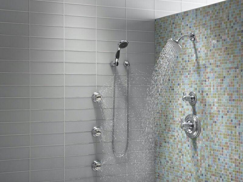 Bad mit gemauerter Dusche und originellen Mosaikfliesen