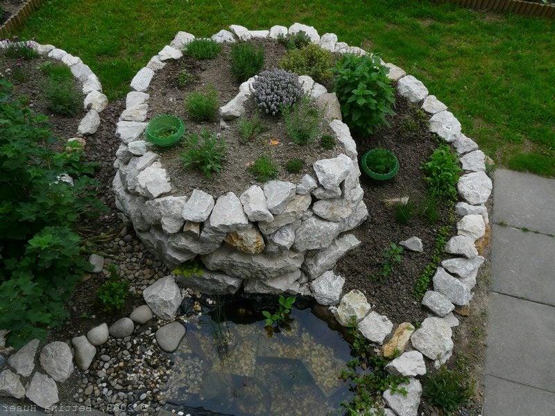 Kräuterschnecke mit dekorativem Teich