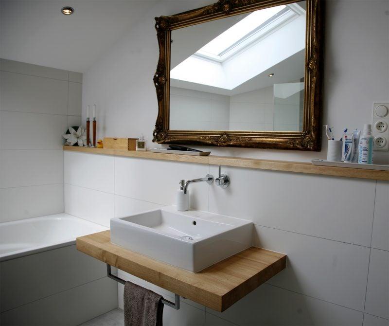 holz waschtischplatte in rustikalem badezimmer mit großem vintage spiegel kombiniert