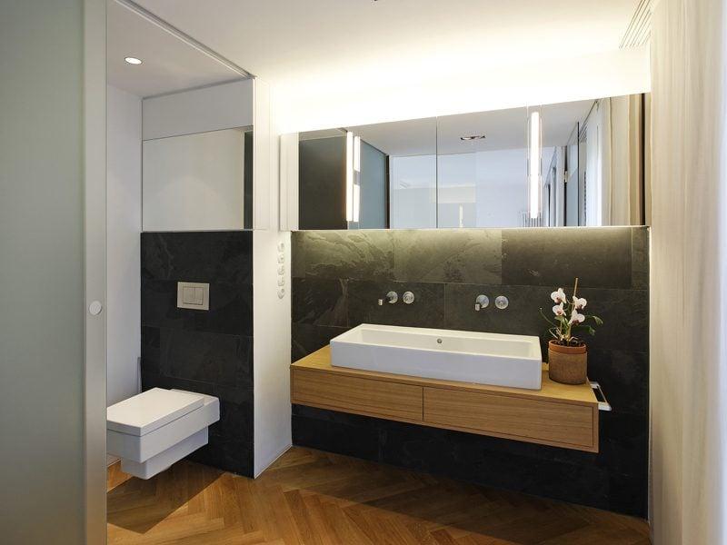 holz waschtischplatte in modernem badezimmer mit schwarzen fliesen und sanfte beleuchtung