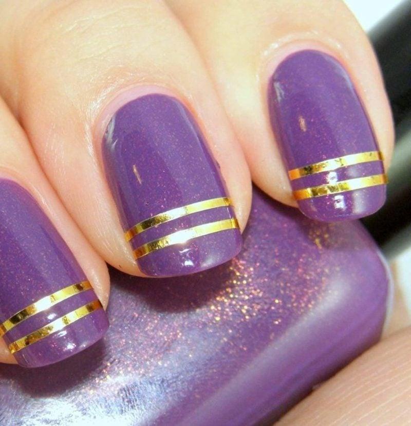 lila Fingernägel mit goldenen Zierstreifen