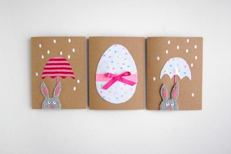 osterkarten auf harten papier mit eier und hasen mit regenschirm und rosa bändchen