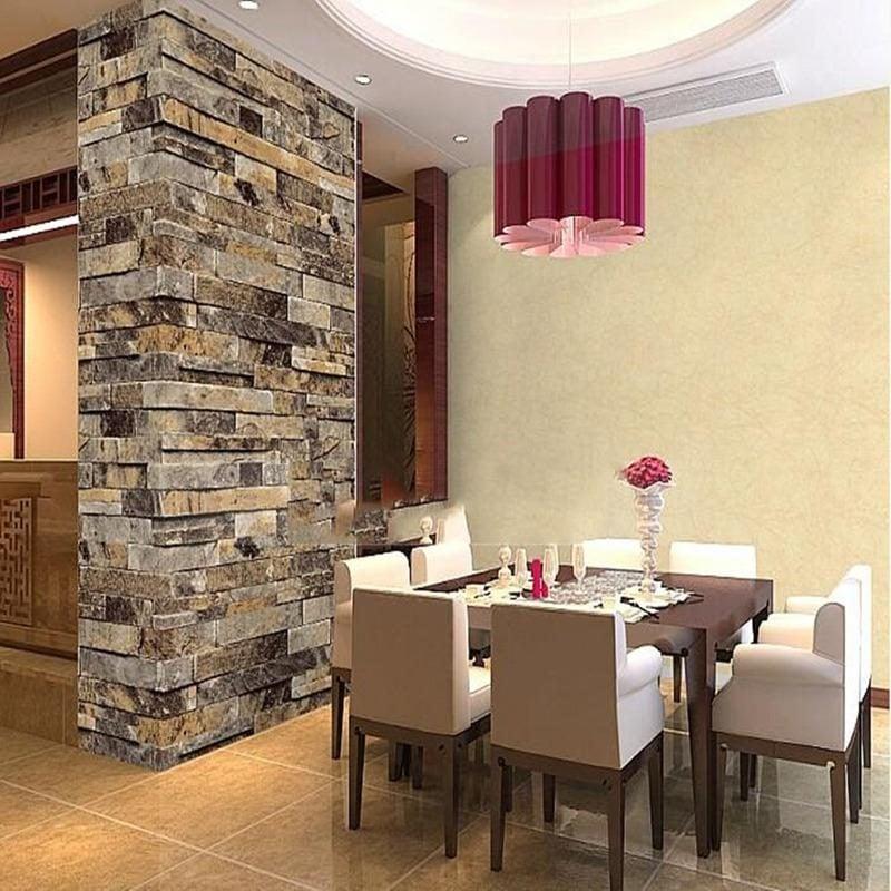 Wandpaneele mit Steinoptik als Trennung zwischen Essbereich und Wohnraum