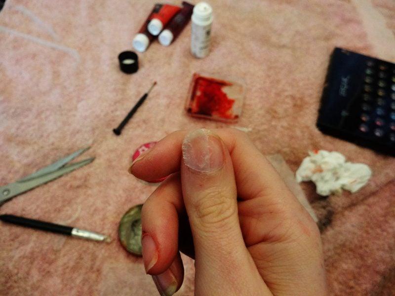 Nehmen Sie einige Stücken von den Tips für künstliche Nägel oder von Plastik