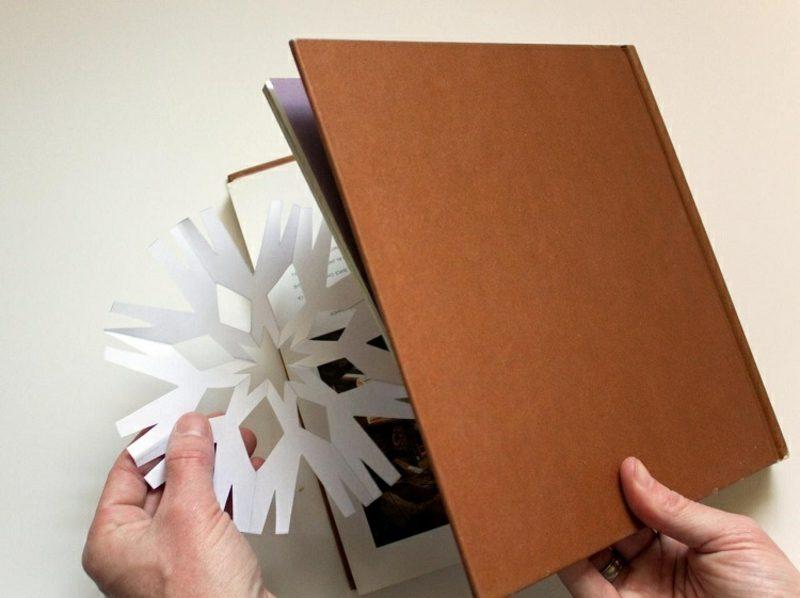 Fensterbilder zu Weihnachten die Schneeflocken zwischen Buchseiten pressen