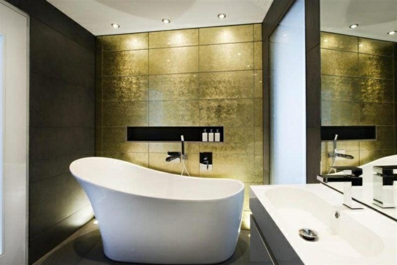 Luxus Badezimmer grosse wanne aus Porzellan goldene Wandfliesen Akzentbeleuchtung