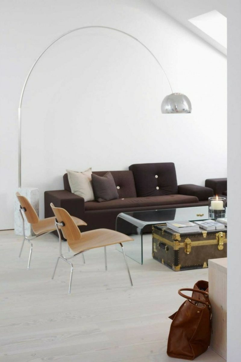 skandinavische Möbel weiches Polstersofa im Schokoladenbraun originelle Lampe aus Edelsahl Couchtisch aus altem Koffer