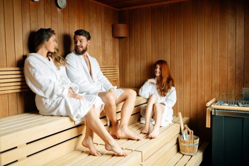 3 entspannte Gäste in einer kleinen Sauna