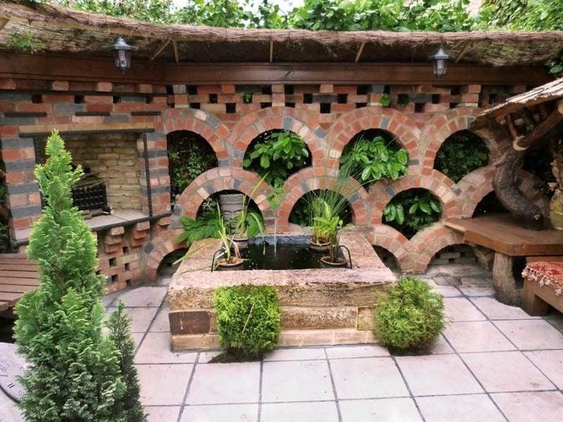 originelle Gartenmauer aus Backsteinen bepflanzt