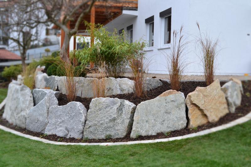 niedrige Gartenmauer aus massiven Steinen