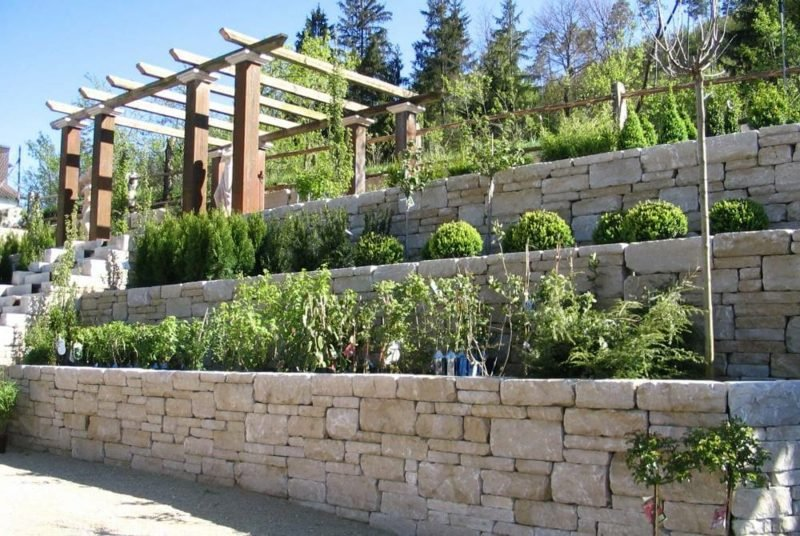 interessante Mauer aus Stein stufenweise gebaut bepflanzt Garten