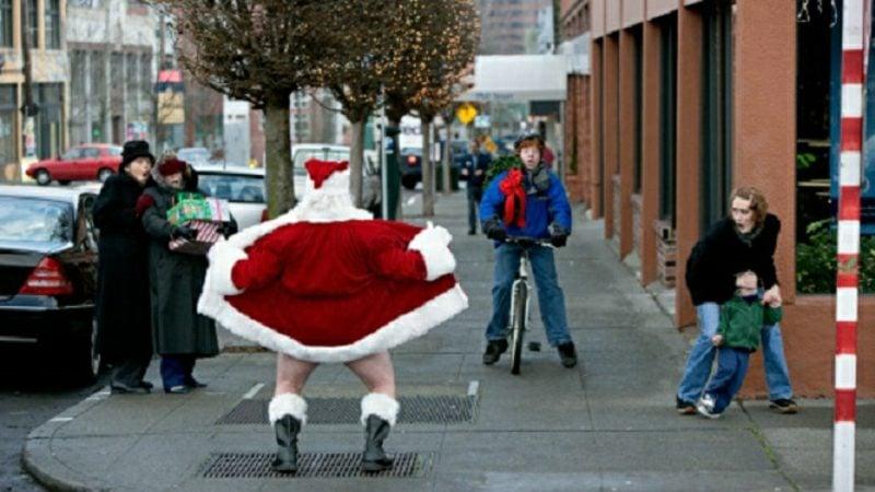 Santa Claus flashing shocked people on a sidewalk