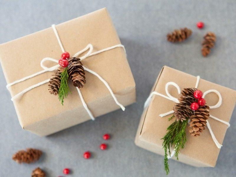 Geschenkpapier zu Weihnachten originelle Dekorationen Tannenzapfen Zweige rote Beeren