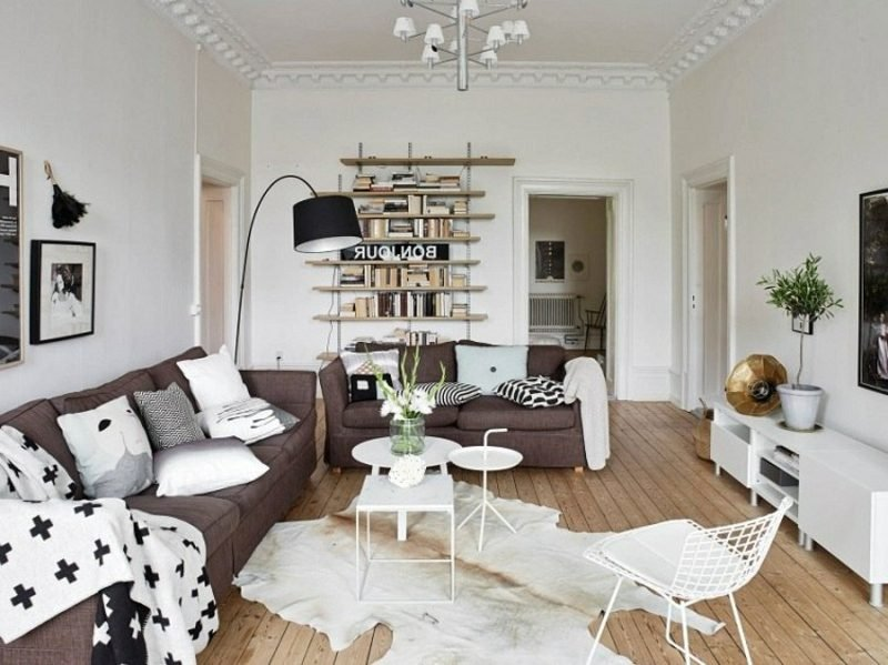 skandinavische Möbel Wohnzimmer zwei braune Polstersofas offenes Regalsystem interessante Lampe aus Edelstahl