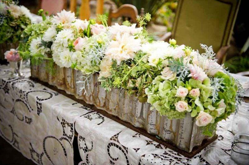Den Tisch mit Blumen dekorieren.