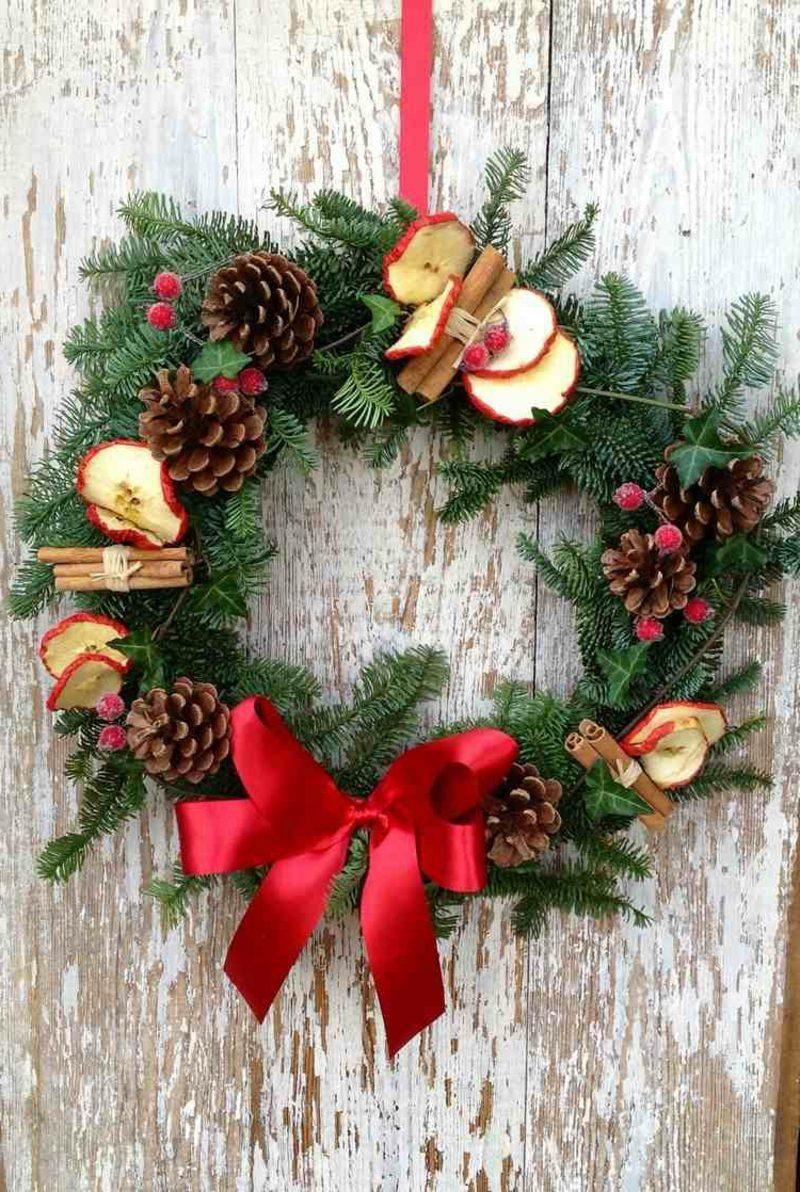 tuerkranz zu weihnachtenturkranz weihnachten tannenzweige zapfen zimtstangen getrocknete aepfel