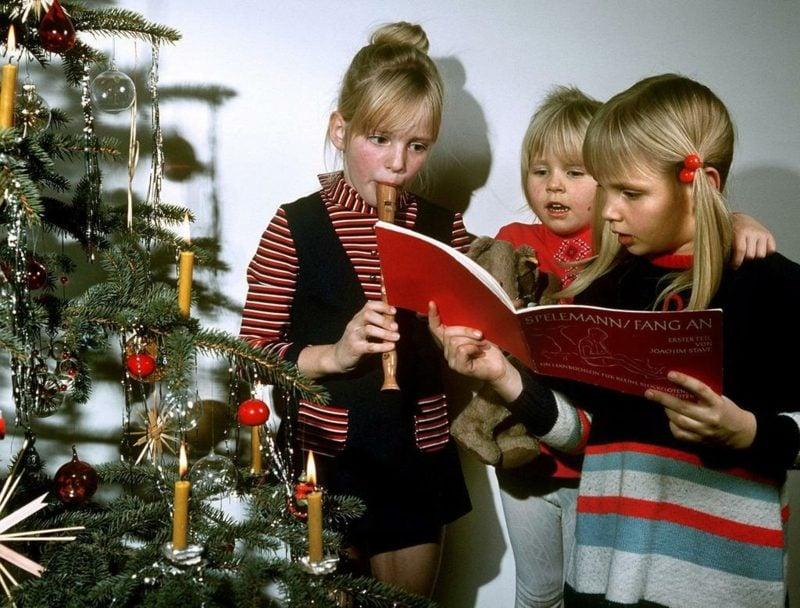Kinder singen Weihnachtslieder beim Tannenbaum