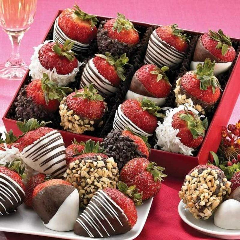 schnelles Fingerfood süss Erdbeeren getaucht in Schokolade und Nüsse