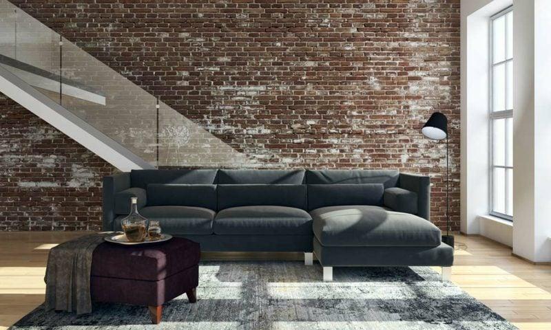 Wohnzimmer gestalten langes Sofa graue Polsterung Ziegelwand
