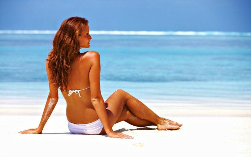 flacher Bauch Frau am Strand fit schlank