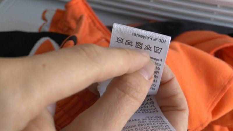 Fettfleck entfernen sich das Etikett das Kleidungsstücks im Voraus ansehen