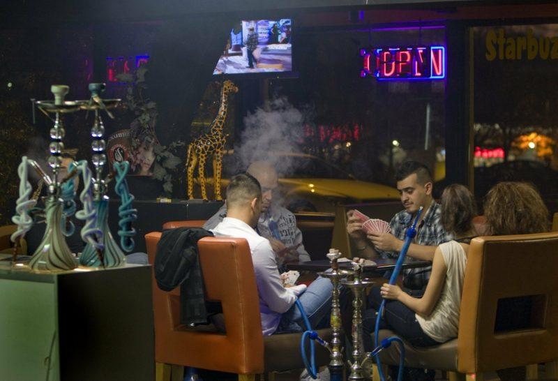 freunde rauchen shisha während kartenspiel
