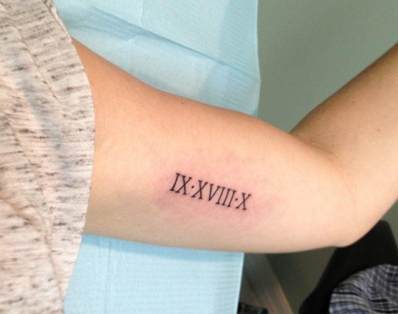 römische Zahlen Tattoo am Oberarm Frau