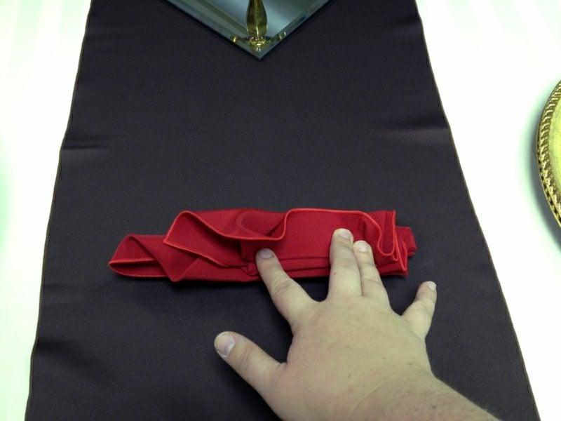Servietten falten zu Weihnachten mit den Fingern festhalten
