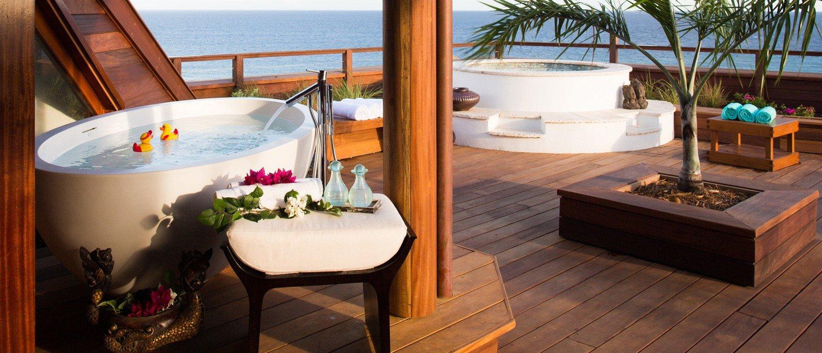 Wollen Sie Ihr Badezimmer in einen Ort der Romantik verwandeln, setzen Sie auf ein paar schöne Glasvasen mit duftenden Blumen und Holzvorleger auf dem Boden.