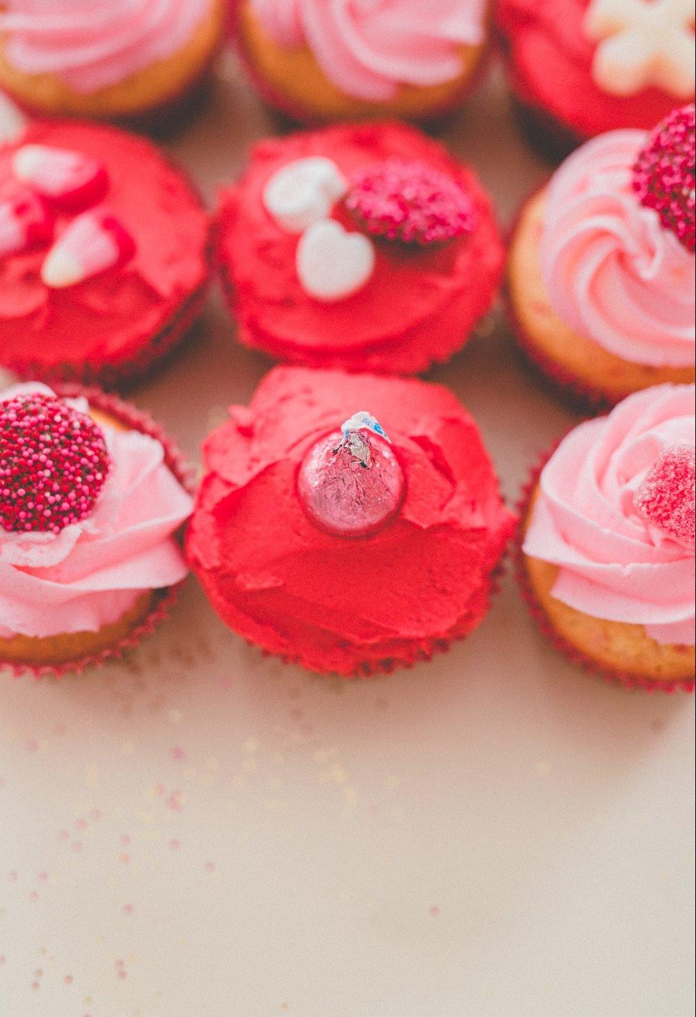 Muffins mit Zuckerglasur in Rosa-Nuancen als eine Idee für Geschenk zum Valentinstag