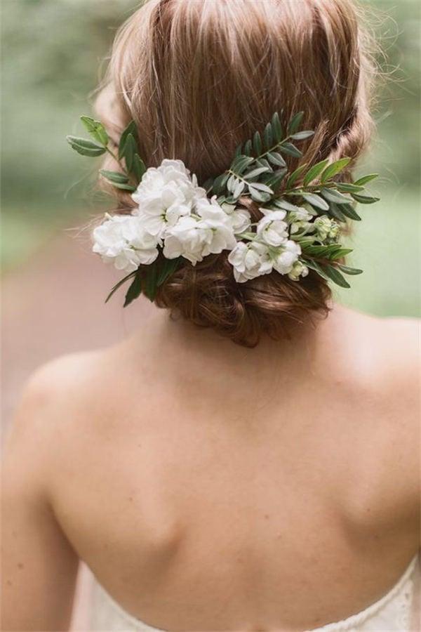 Die schöne Hochsteckfrisur mit frischen Blumen wirkt romantisch