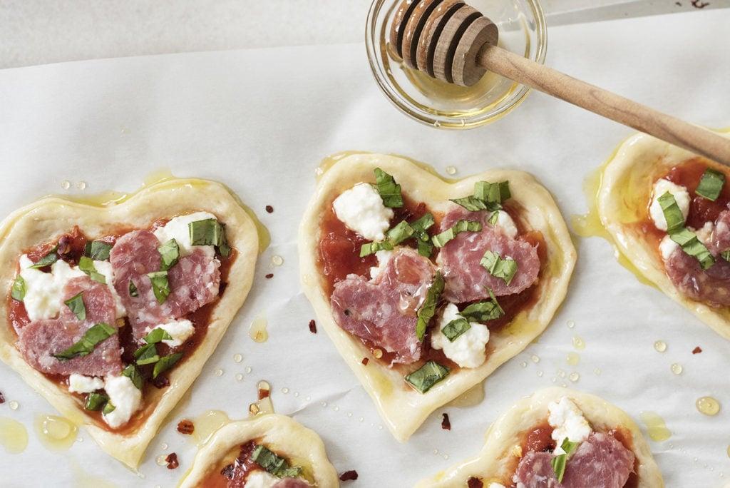 Das Rezept für Herz-Pizza - Schritt 3: Stellen die Herz-Häppchen auf Backpapier im Blech