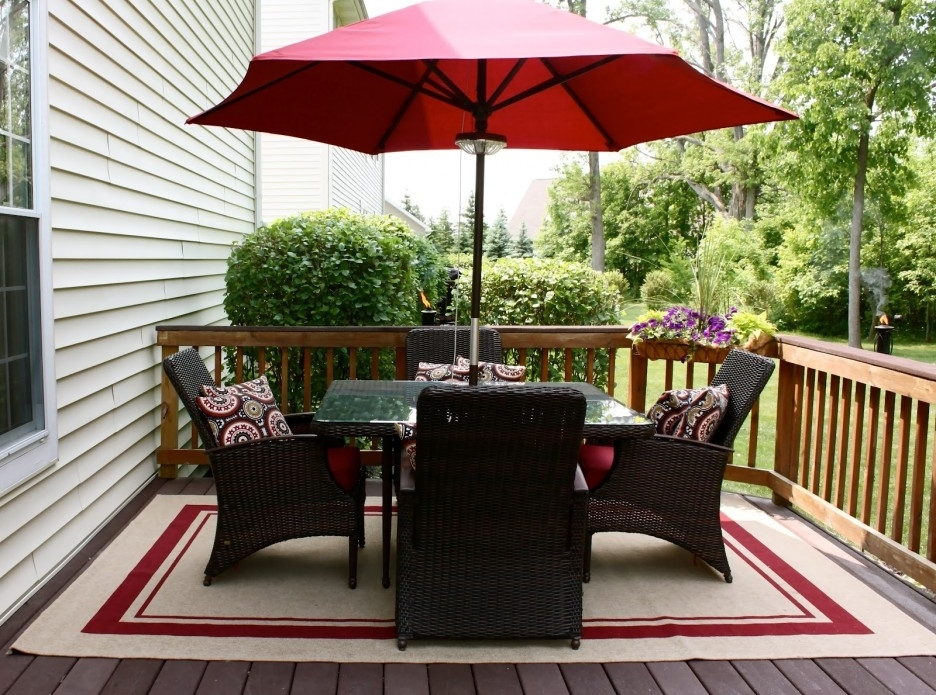 Balkongestaltung mit Sonnenschirm und Teppich