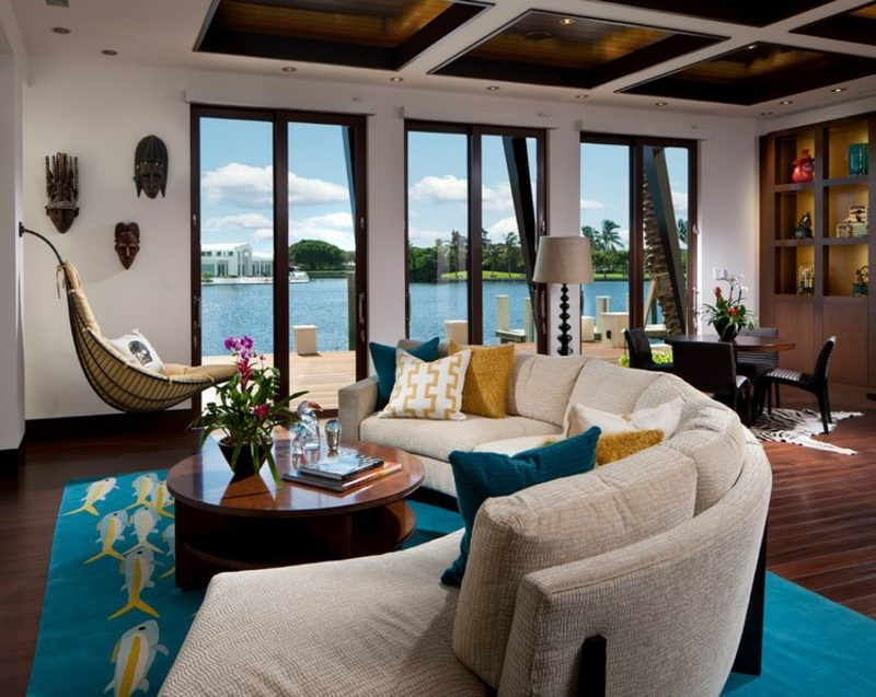 rundes Sofa beige bunte Kissen blauer Teppich