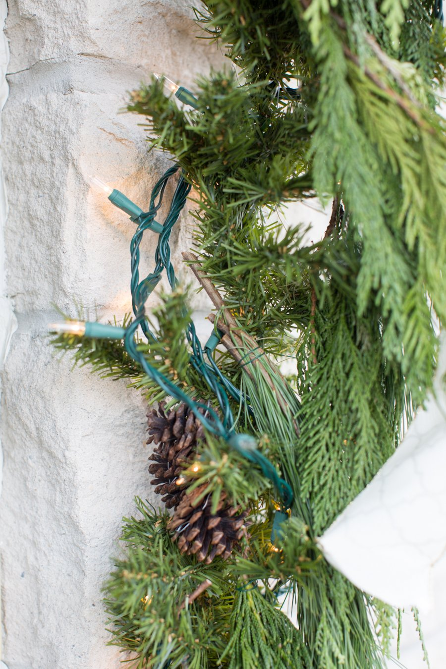 Weihnachtsdeko draußen: Girlande aus immergrünen Pflanzen, Lichterkette und Tannenzapfen