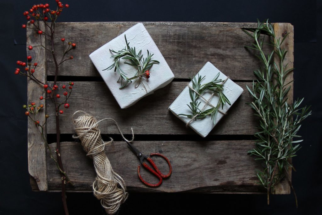 Geschenke einpacken: Der weihnachtliche Kranz kann nicht nur an der Tür hängen, sondern auch auf das Geschenk legen.