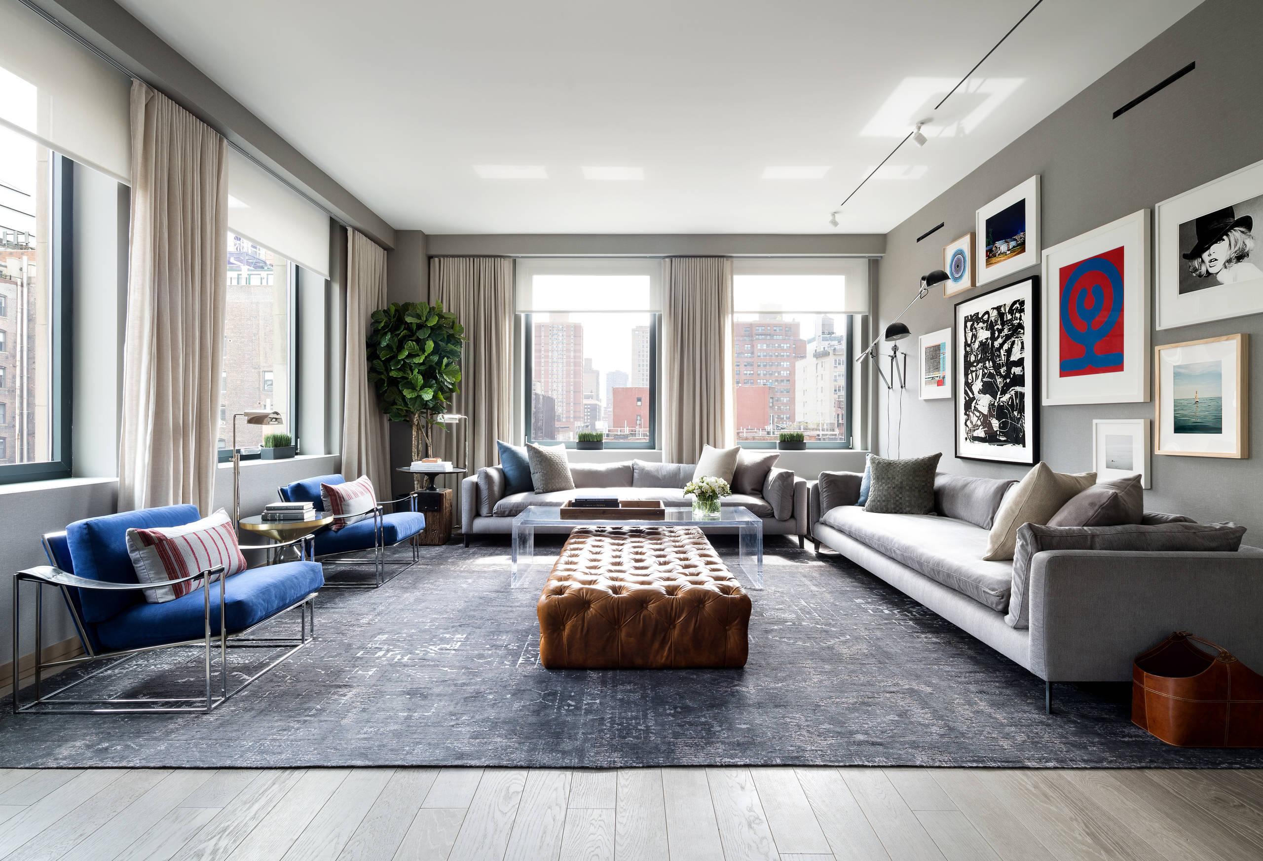 Das Wohnzimmer Grau gestalten: Weder die blauen Sessel noch die Wandgestaltung mit Bildern sind der Blickfang im Wohnzimmer, sondern die Lederbank in der Mitte des Raums.