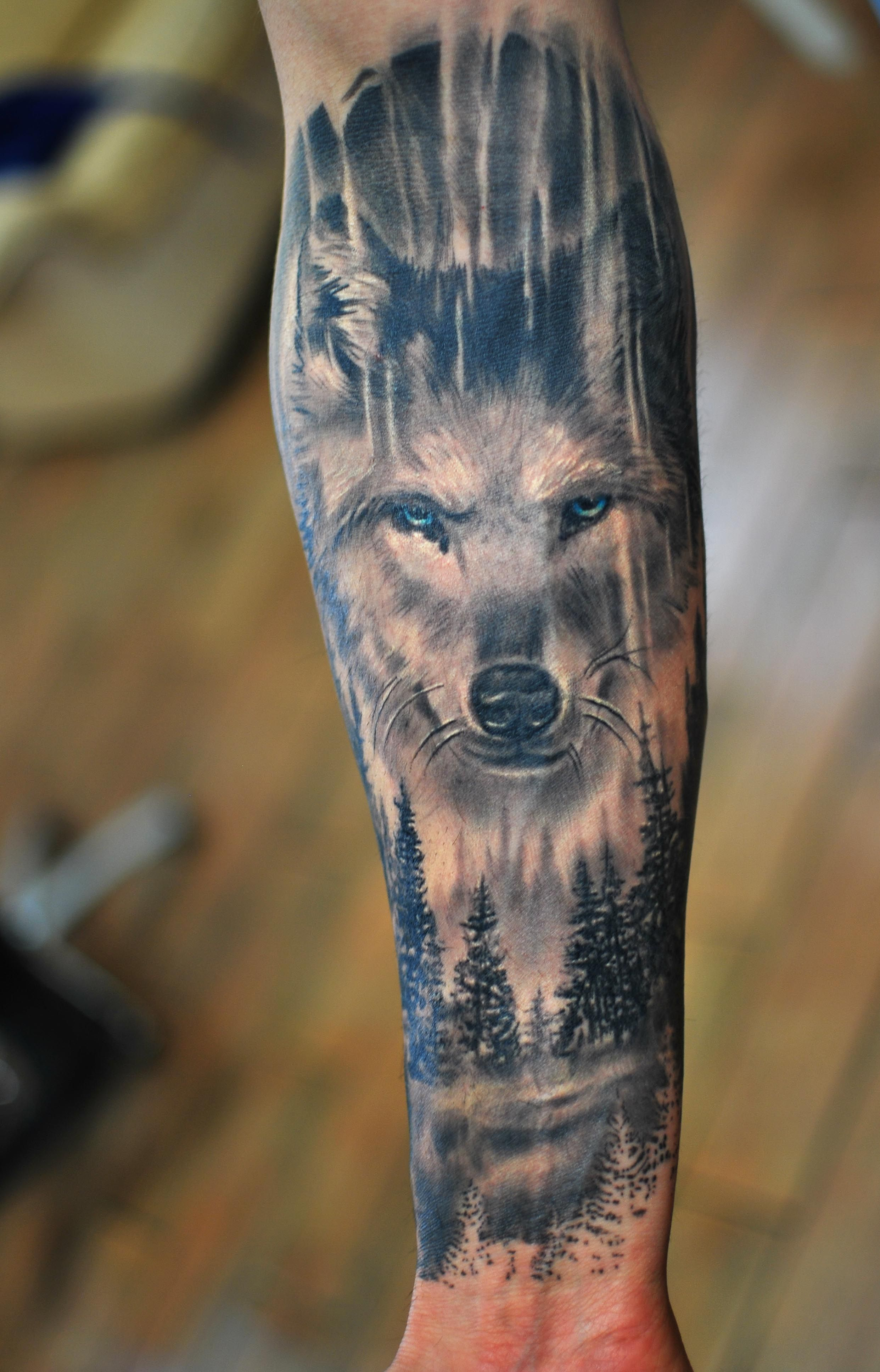 Wolf Tattoo blaue Augen Wald