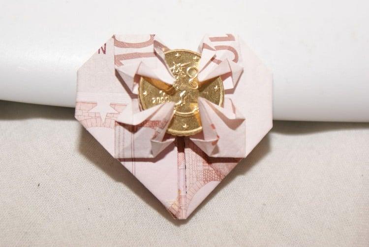 Herz aus Geldschein mit Münze in der Mitte