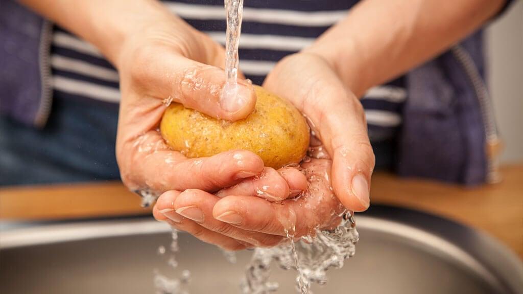 Erdäpfel unter fließendem Wasser waschen