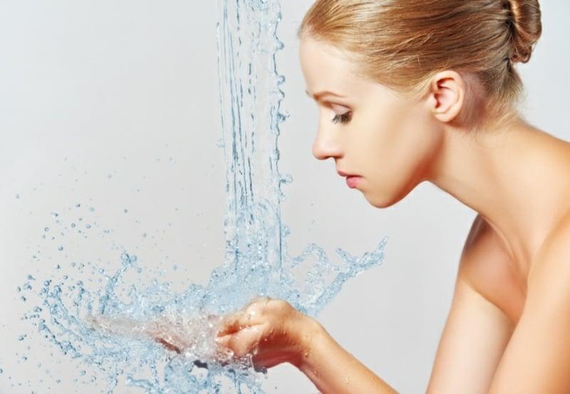 sich das Gesicht mit lauwarmem Wasser waschen