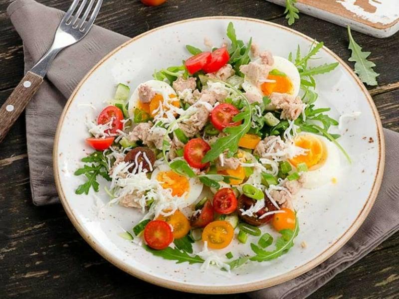 Salat mit gekochten Eiern Kirschtomaten Fisch