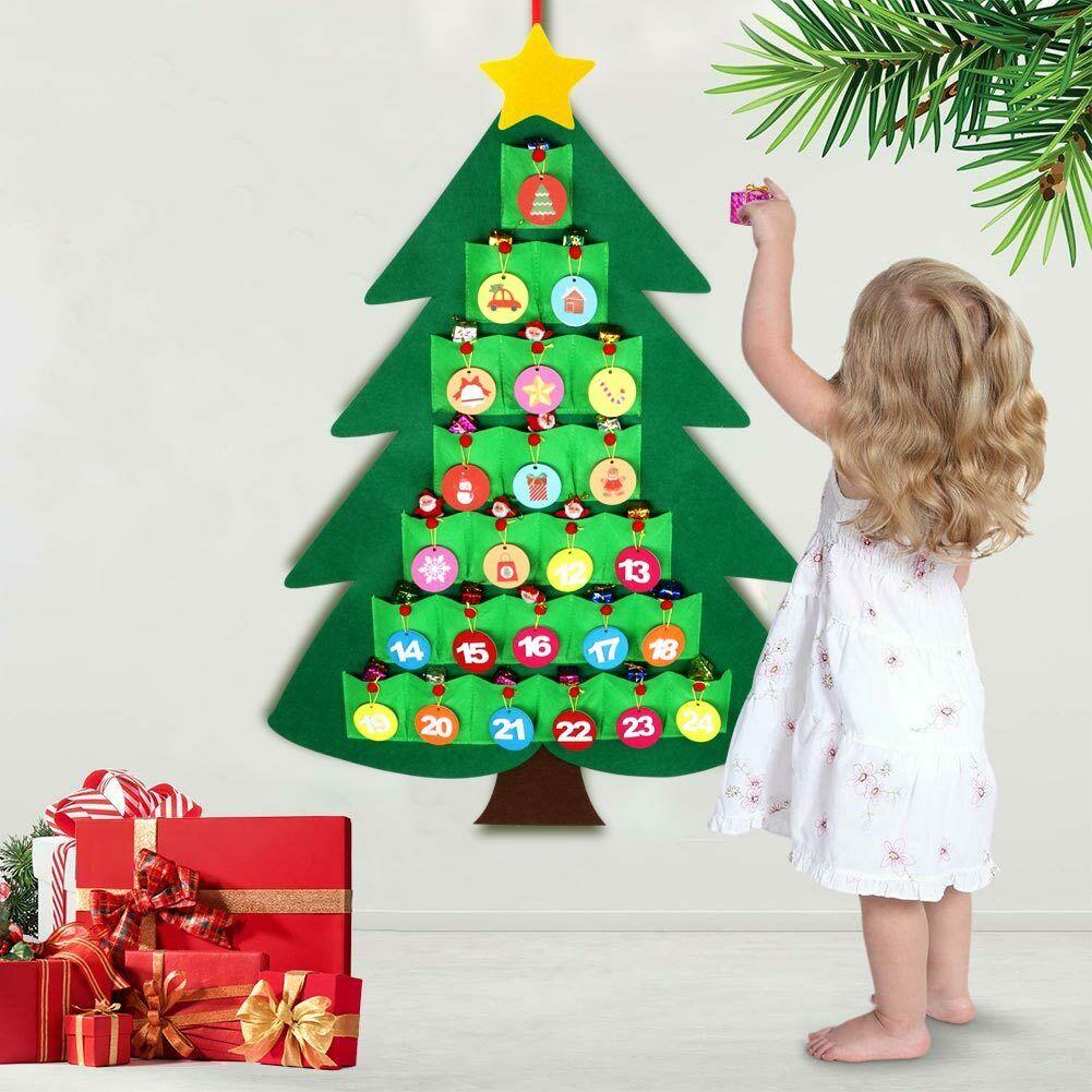 Klein Mädchen füllt mit Geschenken ihren wiederverwendbaren Adventskalender
